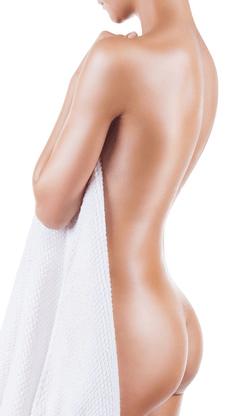 Eine Frau mit einem Handtuch wo der Rücken und der Hintern zu sehen sind.